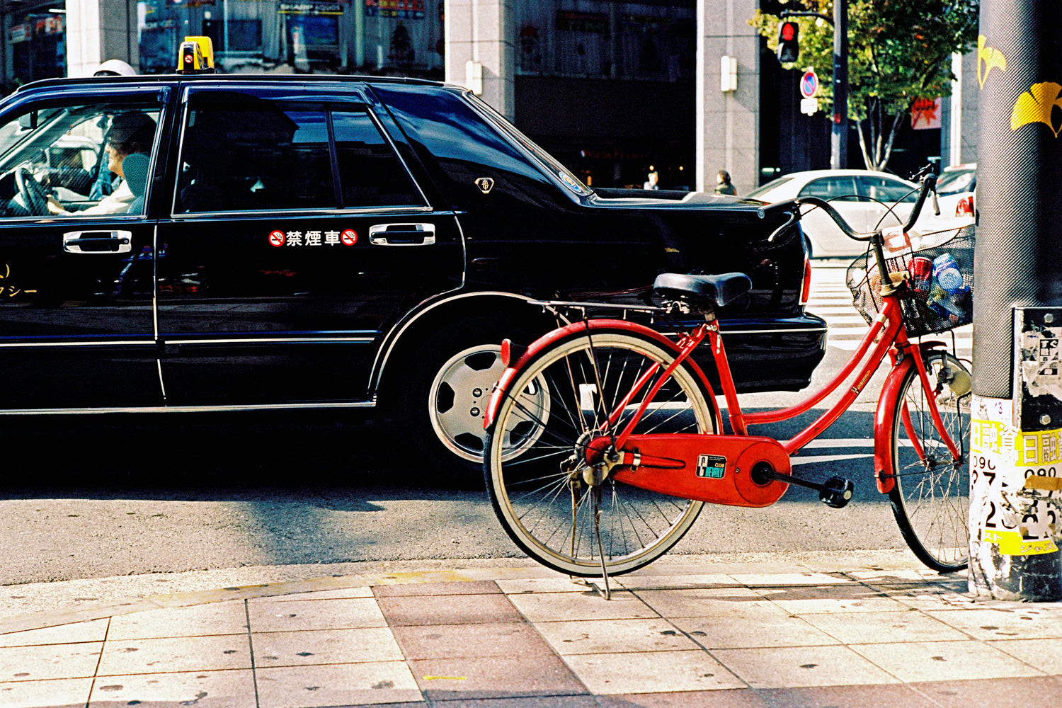 A photograph of a red bike leaning on a pole in a city street in Tokyo. There is a black taxi in the street.  Tokyo Japan.