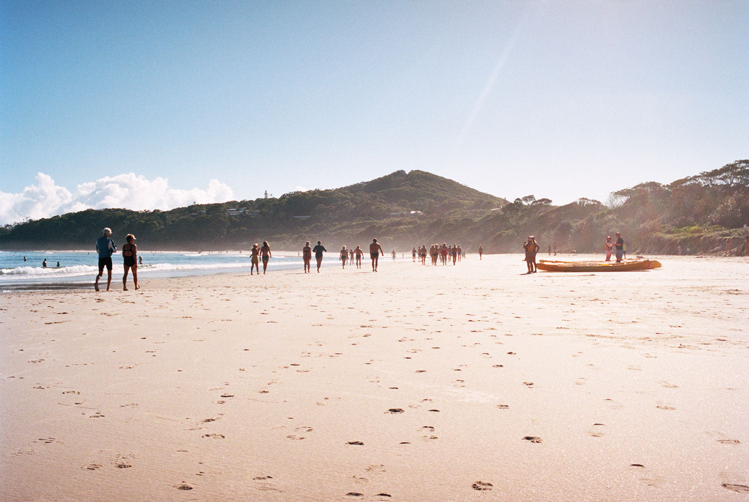 Byron bay beach with people walking in the distance, blue calm water, blue sky. Two men on a kayak head to the water