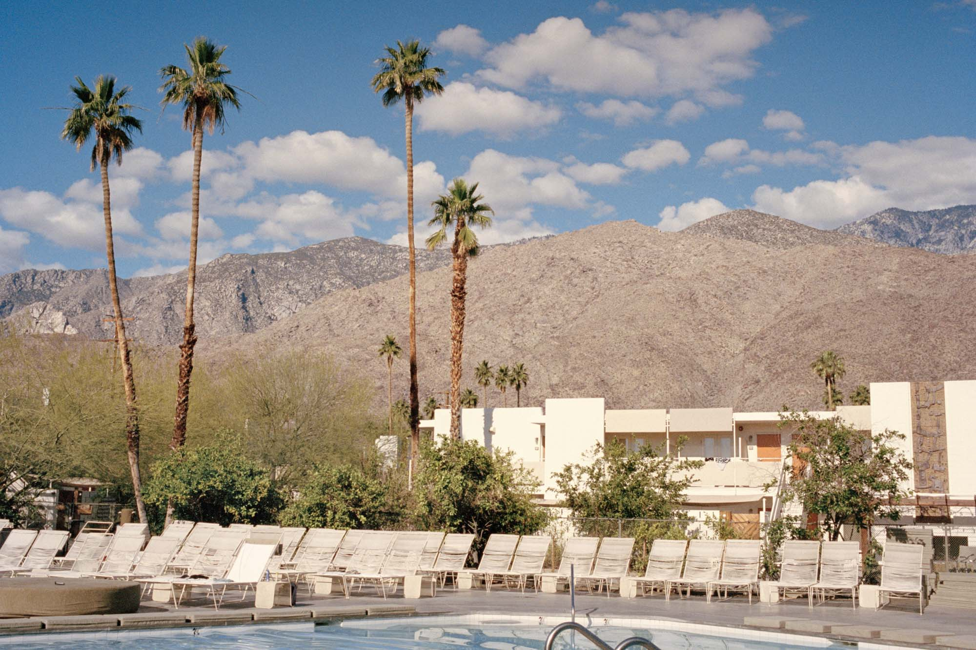 A photograph of a swimming pool looking out on palm trees & large mountains. Blue skies, clouds & Palm trees. USA,