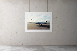 A photographic gallery framed picture of a 1970's single engine plane on a lonely tarmac in California