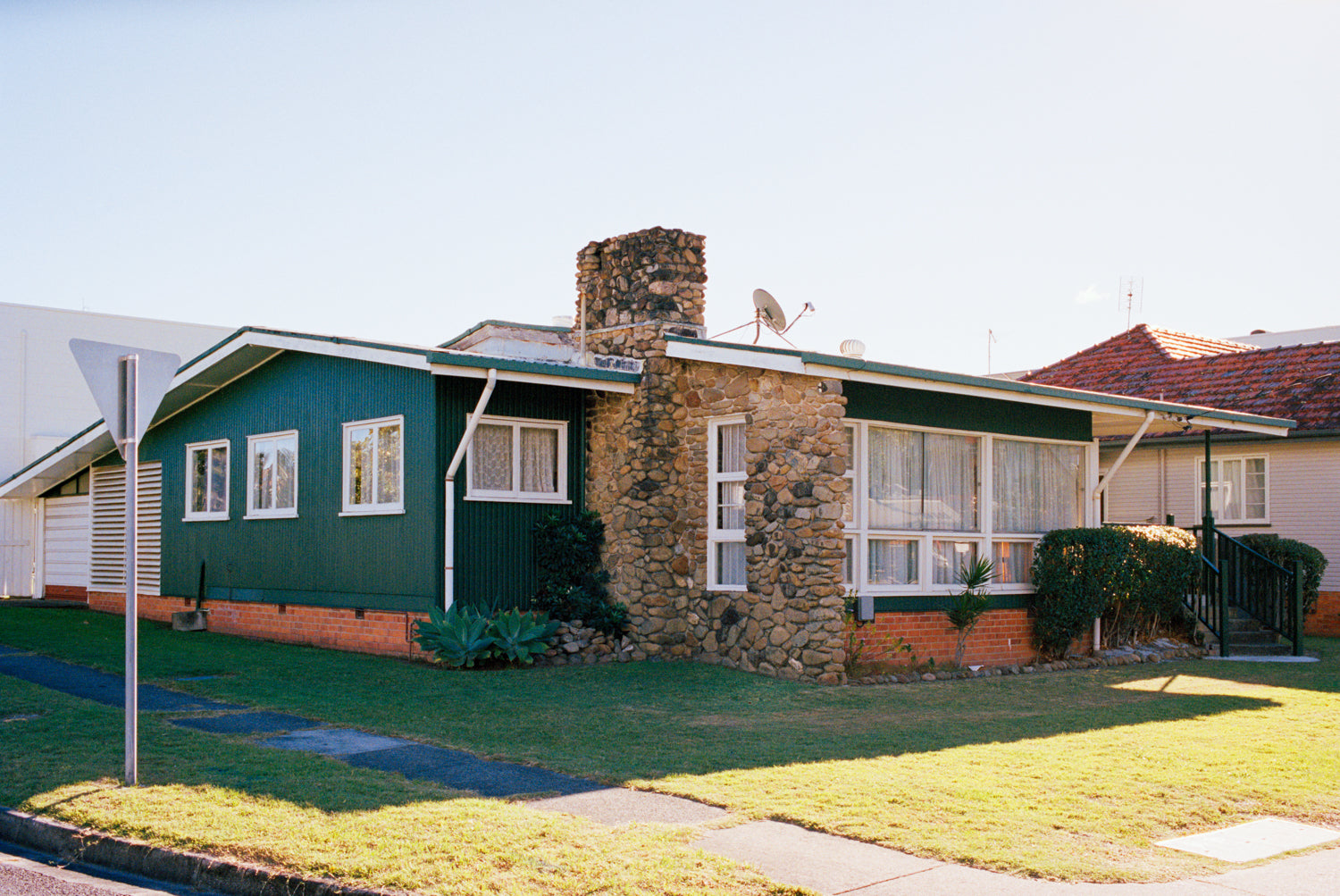 A photograph of a 1960's timber house on the Goldcoast. The house is green with a large stone fireplace & chimney, blue skies.