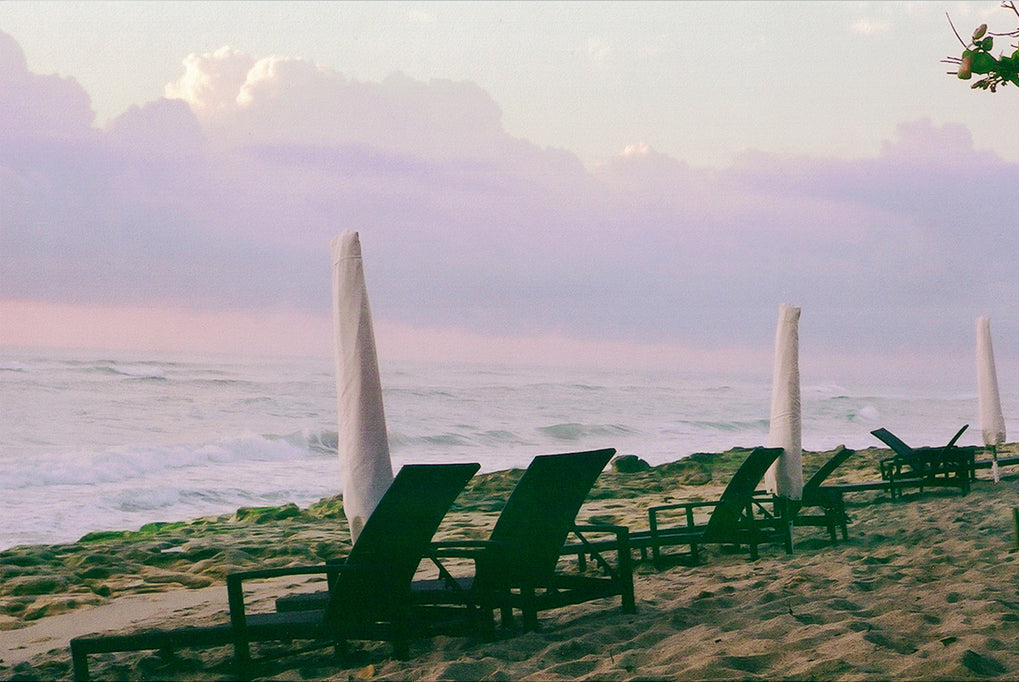 Miami beach with black sun lounges & white umbrella's, purple skies & clouds, sand & blue calm water.
