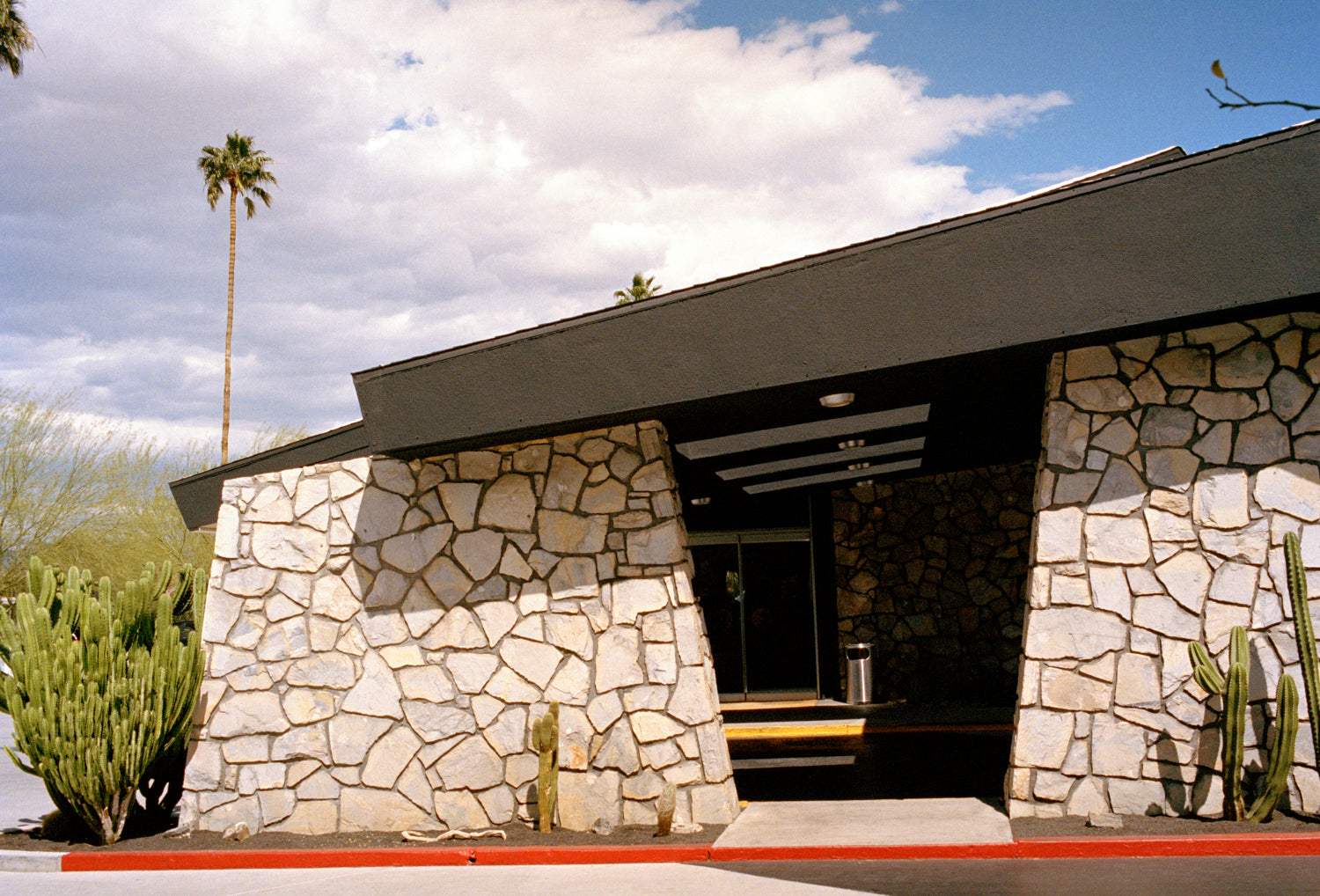A photography of the Ace Hotel stone wall in Palm Springs. A rmid century stone building.