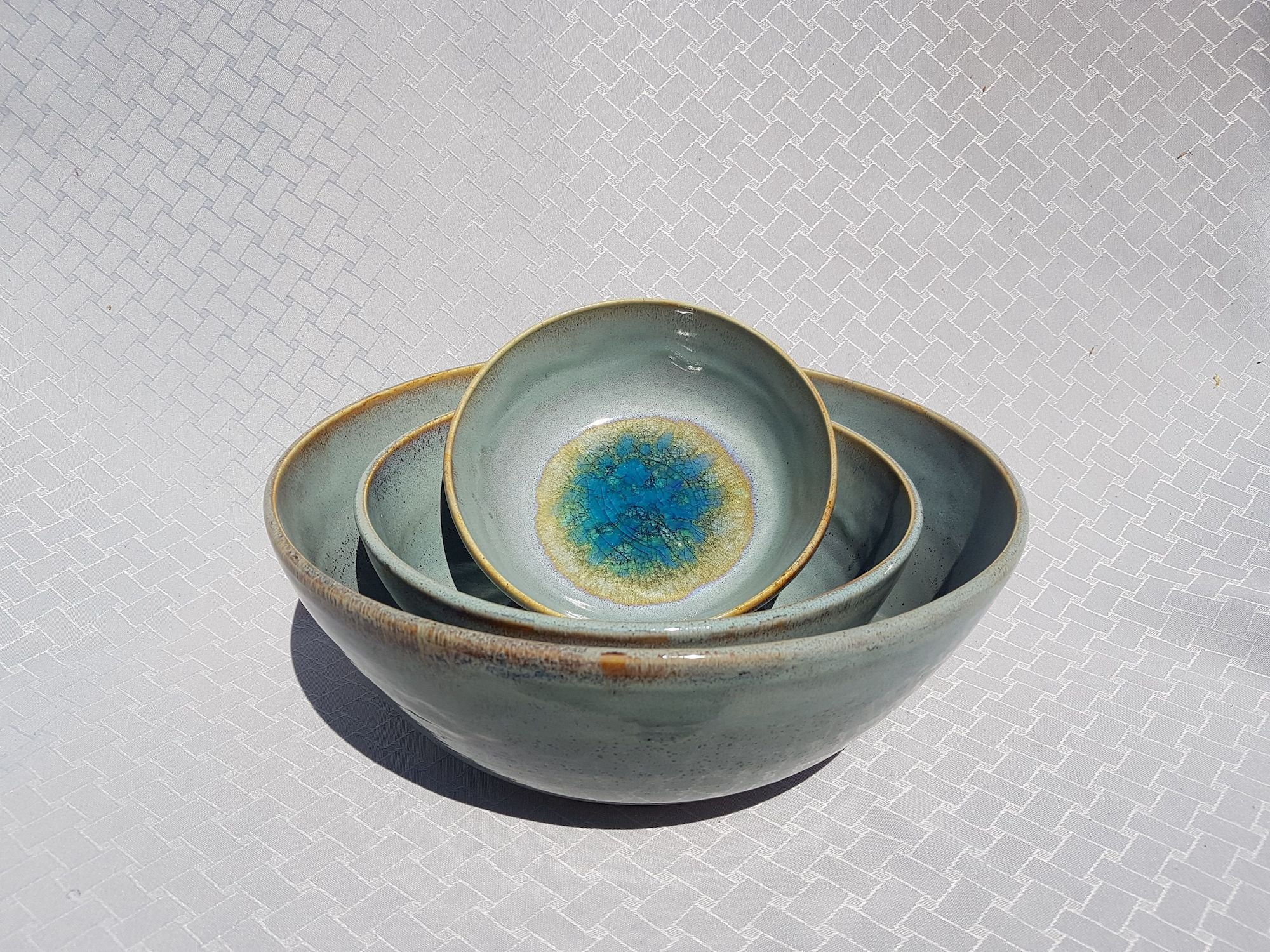 A pale grey/blue glaze with sand toned speckles