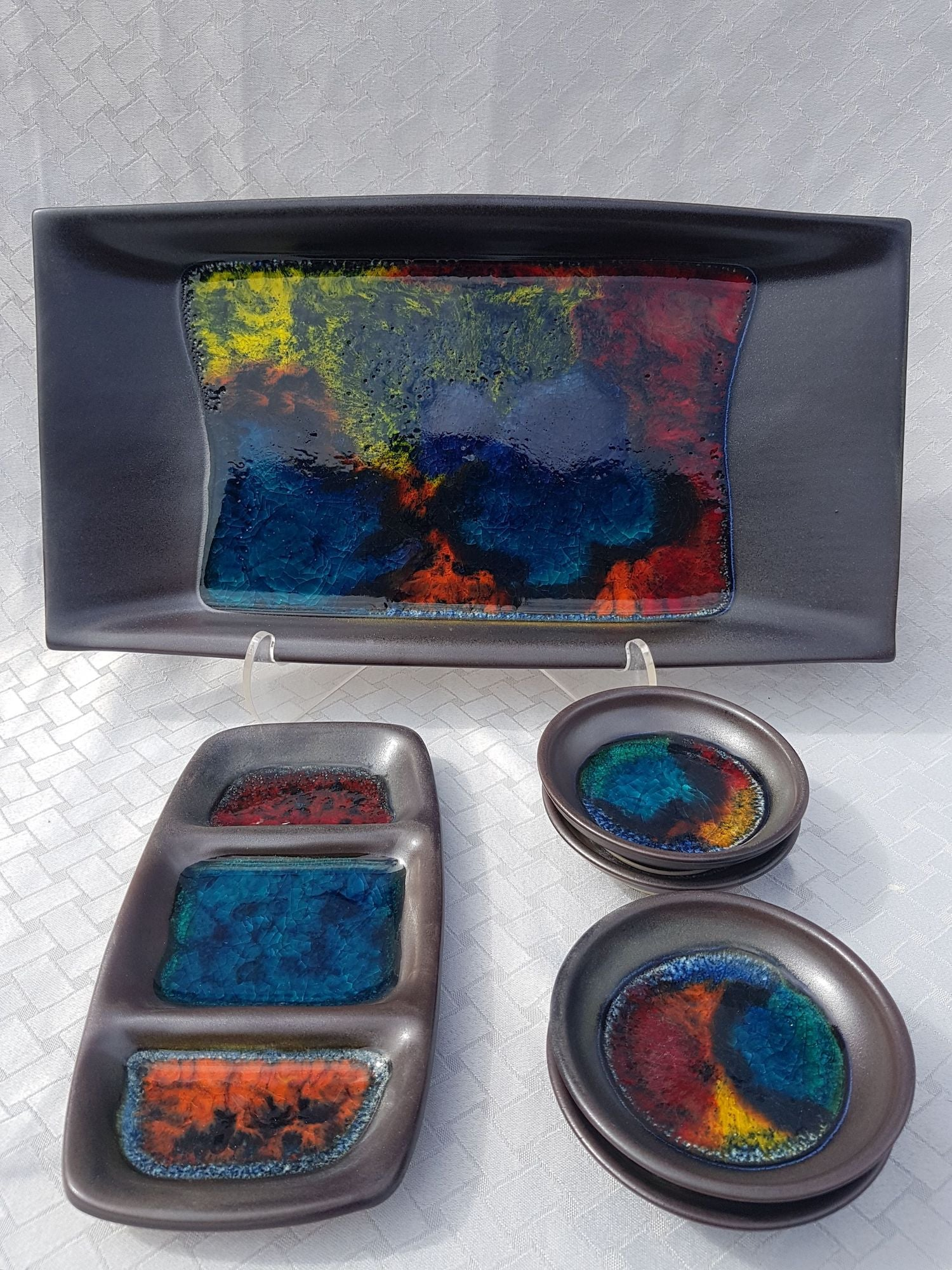 A semi-matte charcoal glaze with vibrant bursts of glossy colour