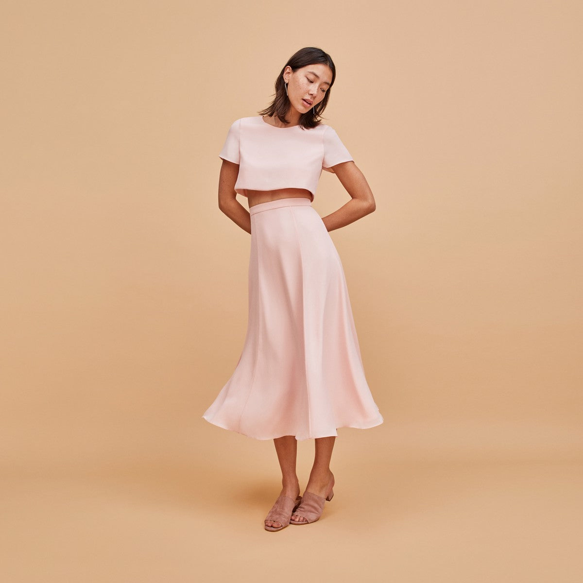 Woman in pale pink two piece dress front.