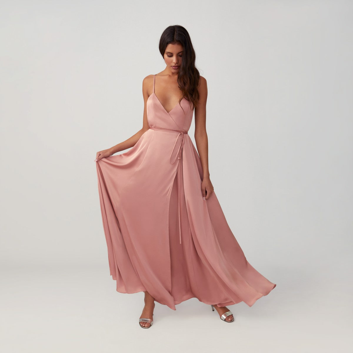 Woman in blush wrap dress front.