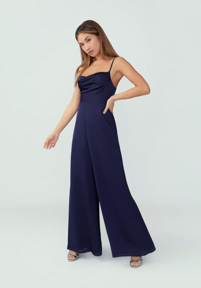 Woman in navy draped wide leg jumpsuit front.
