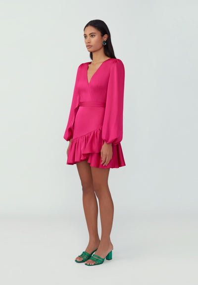 Woman in hot pink ruffled asymmetric wrap dress front.