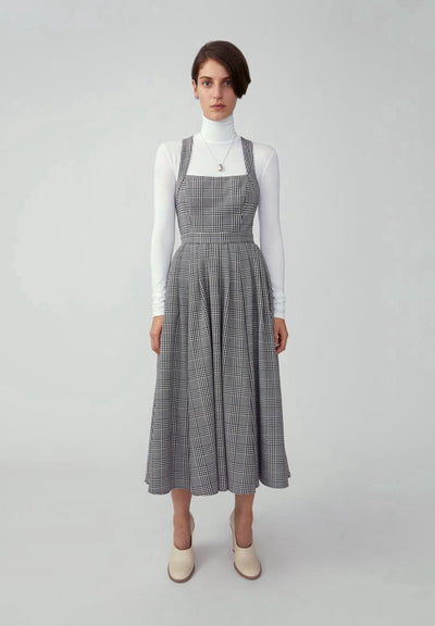 Woman in houndstooth grey fitted bodice midi dress front.
