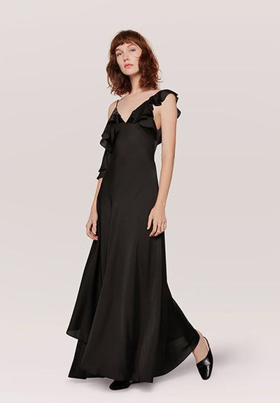 Woman in black off shoulder asymmetrical dress front.