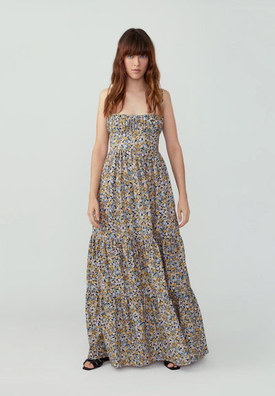 Woman in floral yellow gathered tiered maxi dress front.