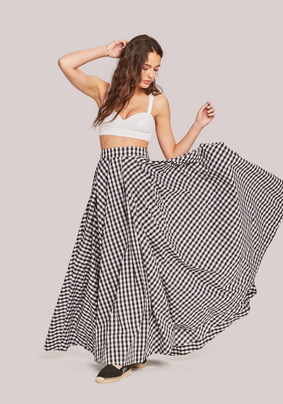 Woman in black and whtie mini checker full skirt front.