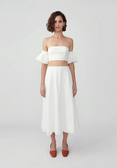 Woman in ivory puff sleeve bandeau top and skirt set front.