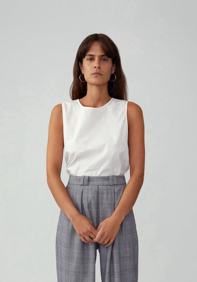 Woman in white shirt gray pant set front.