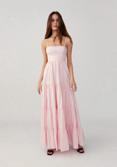Woman in pretty pink gathered tiered dress front.