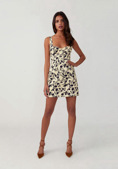 Woman in silhouette pale yellow mini dress front.