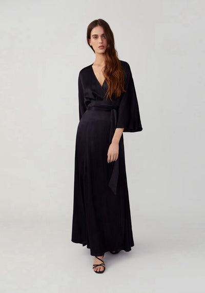 Woman in crepe black slim fitting true wrap dress front.