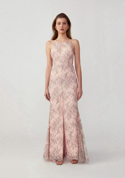 Woman in printed pale pink mermaid flared skirt dress front.