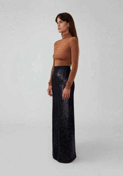 Woman in sequin black flared maxi skirt side.