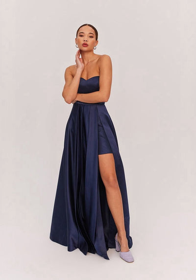 Woman in navy strapless maxi dress front.