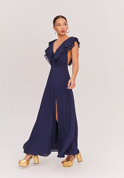 Woman in navy ruffled maxi dress front.
