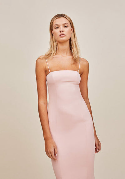 Woman in pale pink slip dress front.