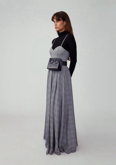 Woman in grey plaid corset maxi dress side.