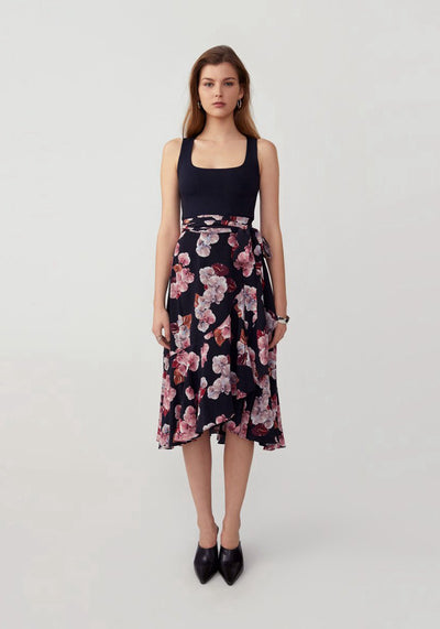 Woman in anthrium black true wrap ruffle skirt front.