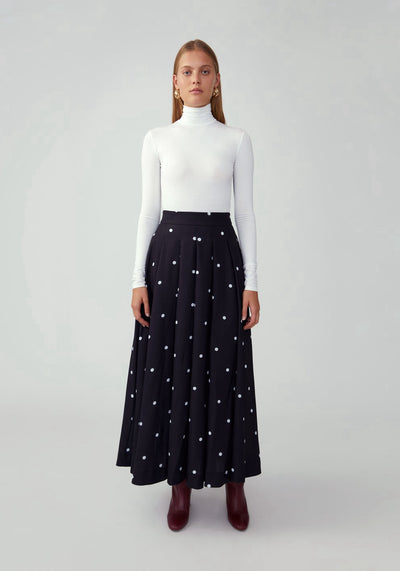 Woman in black and white spot high waist skirt front.
