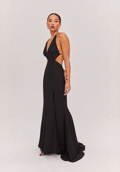 Woman in black plunging neckline maxi dress side.