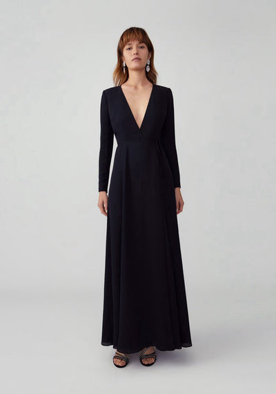 Woman in black wrap dress front.