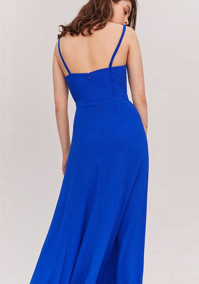 Woman in cobalt maxi dress back.