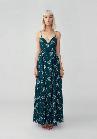 Woman in dark forest V-neck open back wrap dress front.