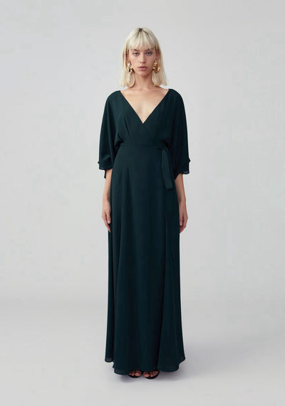 Woman in dark forest balloon sleeve maxi gown front.