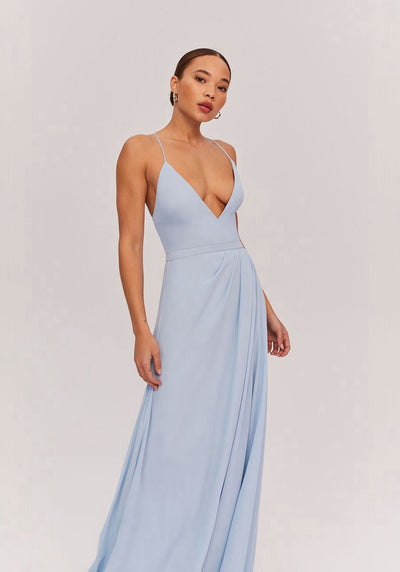 Woman in light blue deep v neck dress front.