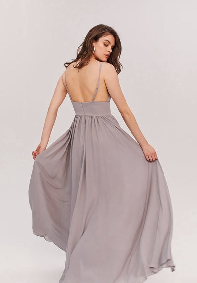 Woman in pale grey deep V neckline maxi dress back.