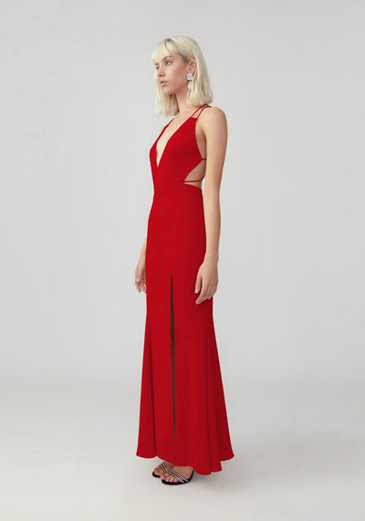 Woman in red v neck side cut out maxi dress side.