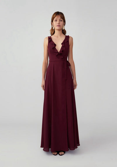 Woman in wine ruffle neckline wrap dress front.