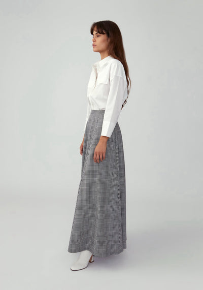 Woman in plaid grey fit and flare maxi skirt side.