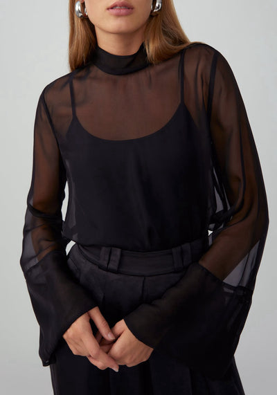 Woman in black chiffon loose long flared sleeve top front.