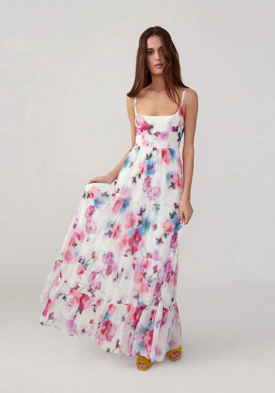 Woman in white printed floral pink dress front.