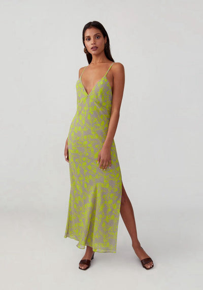 Woman in printed silhouette citron V-neck slip dress front.