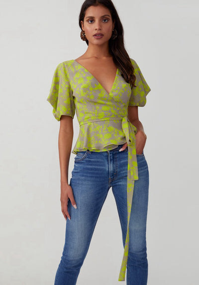 Woman in printed citron wrap top front.