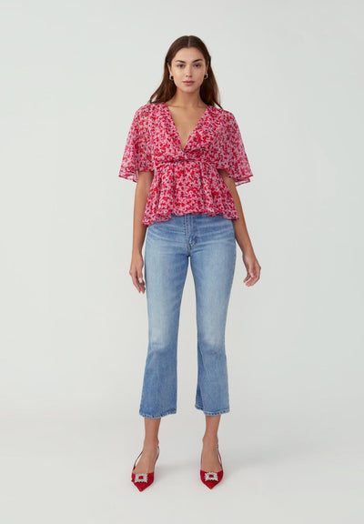 Woman in printed confetti floral red winged sleeve top front.
