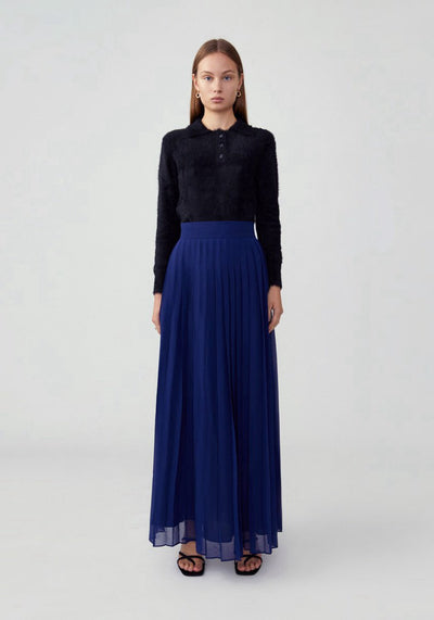 Woman in atlantic blue a-line pleated skirt front.