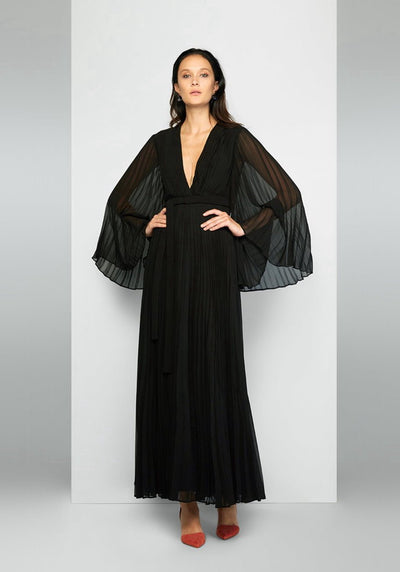 Woman in black v neck balloon sleeve dress front.
