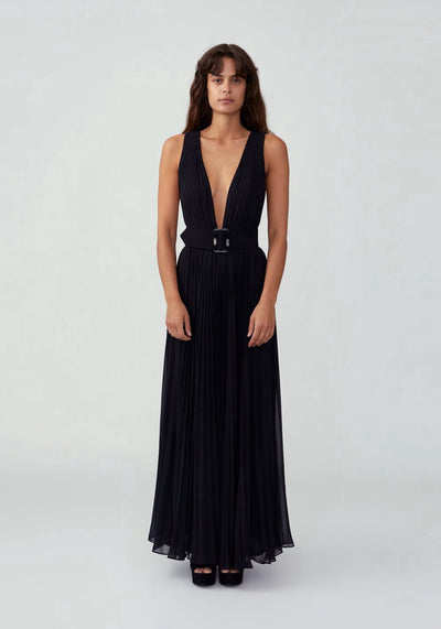 Woman in black plunging pleated jumpsuit front.
