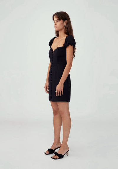 Woman in black full button front mini dress side.