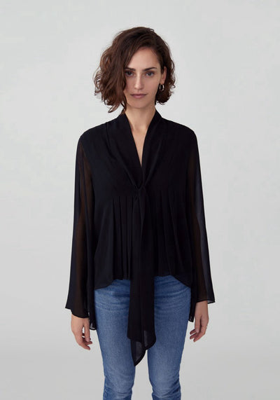 Woman in black loose fitting bow tie blouse front.